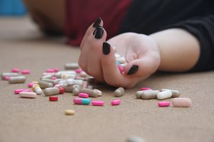 Drugs and pills are scattered on the floor and spill out of a lady's hand