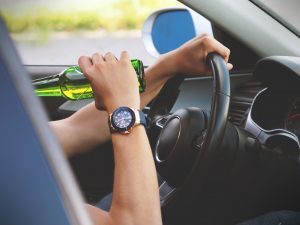Picture of a person drinking while driving.