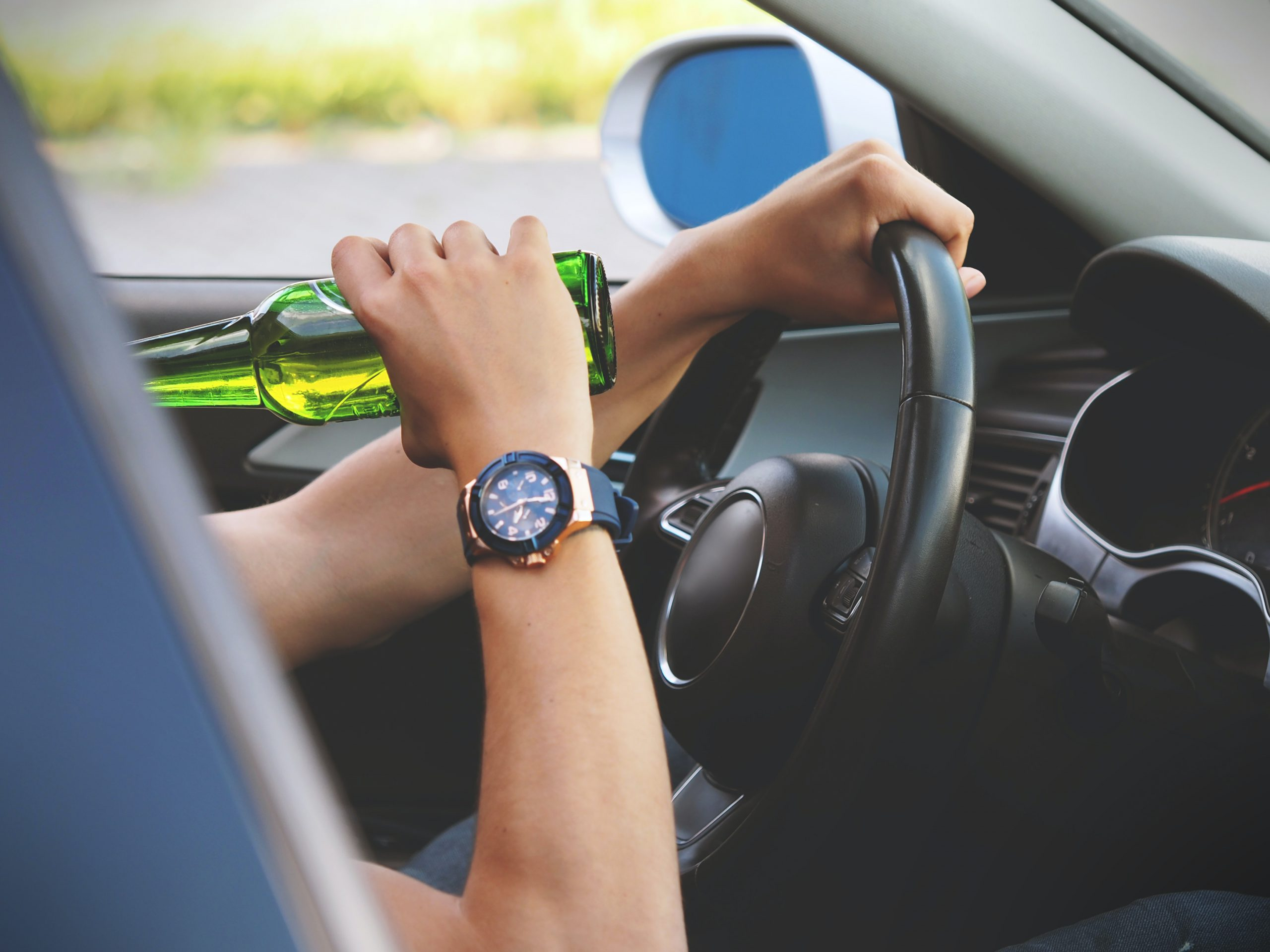 Picture of a person drinking beer while driving a car.